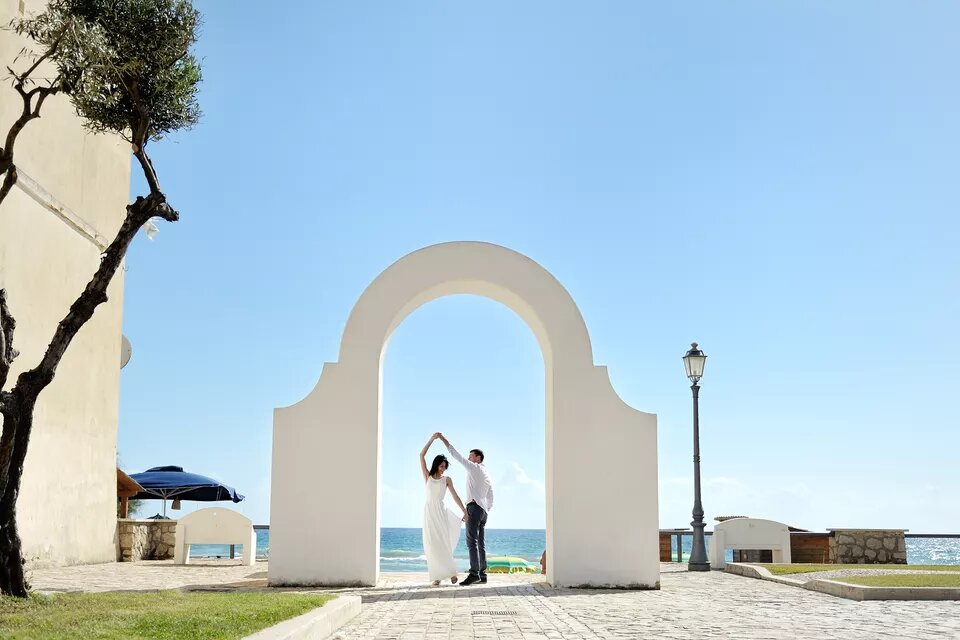 Newlyweds in Italy outside below wedding arch